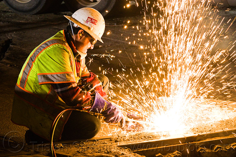 welder cutting rail with oxy-acetylene torch, high-visibility jacket, high-visibility vest, light rail, man, muni, night, ntk, oxy-acetylene cutting torch, oxy-fuel cutting, railroad construction, railroad tracks, railway tracks, reflective jacket, reflective vest, safety glasses, safety gloves, safety helmet, safety vest, san francisco municipal railway, sparks, track maintenance, track work, welder, worker