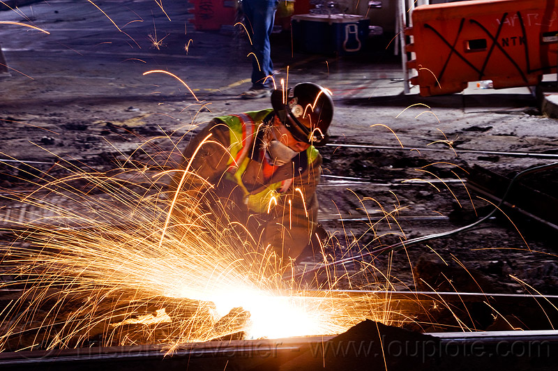welder cutting rail with oxy-acetylene torch, demolition, high-visibility jacket, high-visibility vest, light rail, man, muni, night, ntk, oxy-acetylene cutting torch, oxy-fuel cutting, railroad construction, railroad tracks, rails, railway tracks, reflective jacket, reflective vest, safety helmet, safety vest, san francisco municipal railway, track maintenance, track work, welder, welding, worker, working