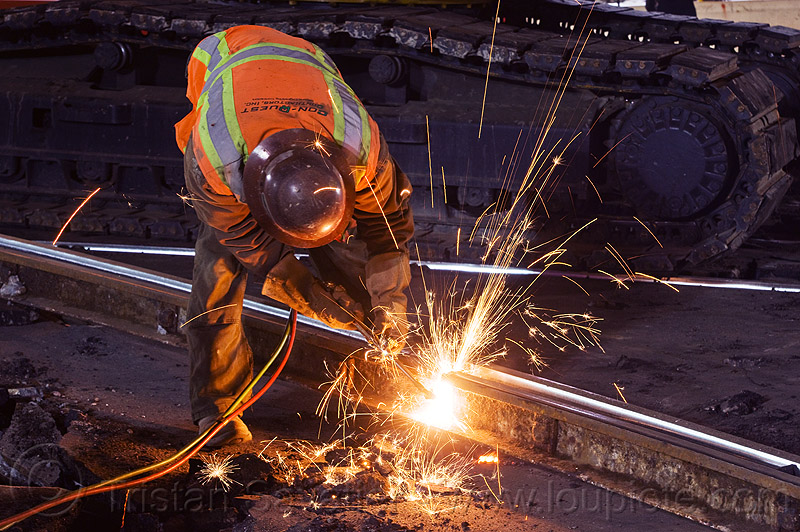 welder cutting a railroad track rail with an oxy-acetylene torch, construction, cutting torch, demolition, helmet, high-visibility jacket, high-visibility vest, light rail, man, muni, night, ntk, oxy-acetylene cutting, oxy-acetylene cutting torch, oxy-fuel, oxy-fuel cutting, people, railroad construction, railroad tracks, rails, railway, railway tracks, reflective, reflective jacket, reflective vest, safety helmet, safety vest, san francisco municipal railway, sparks, track maintenance, track work, welding, worker, working