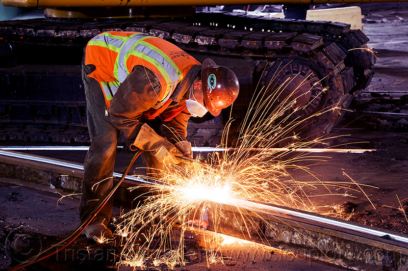welder cutting a track rail with an oxy-acetylene torch, demolition, high-visibility jacket, high-visibility vest, light rail, man, muni, night, ntk, oxy-acetylene cutting torch, oxy-fuel cutting, railroad construction, railroad tracks, railway tracks, reflective jacket, reflective vest, safety helmet, safety vest, san francisco municipal railway, sparks, track maintenance, track work, welder, welding, worker, working