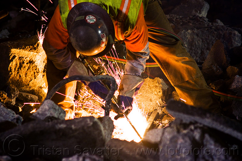 welder cutting a track rail with a oxy-acetylene torch, high-visibility jacket, high-visibility vest, light rail, man, muni, night, ntk, oxy-acetylene cutting torch, oxy-fuel cutting, railroad construction, railroad tracks, railway tracks, reflective jacket, reflective vest, safety glasses, safety gloves, safety helmet, safety vest, san francisco municipal railway, sparks, track maintenance, track work, welder, worker, working