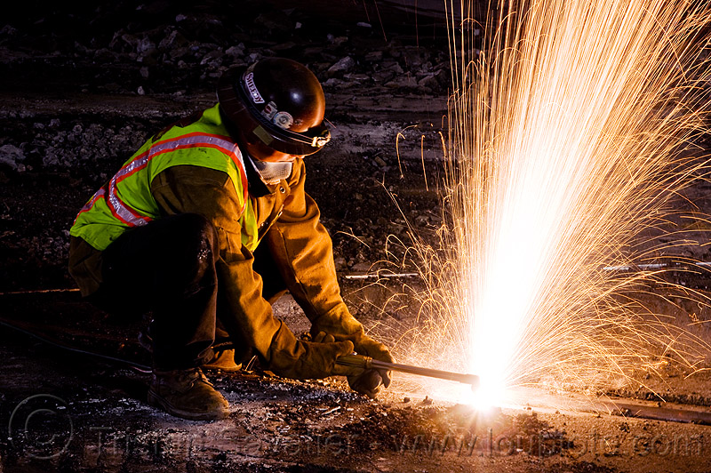 welder cutting a train rail with an oxy-acetylene torch, demolition, high-visibility jacket, high-visibility vest, light rail, man, muni, night, ntk, oxy-acetylene cutting torch, oxy-fuel cutting, railroad construction, railroad tracks, railway tracks, reflective jacket, reflective vest, safety helmet, safety vest, san francisco municipal railway, sparks, track maintenance, track work, welder, welding, worker, working