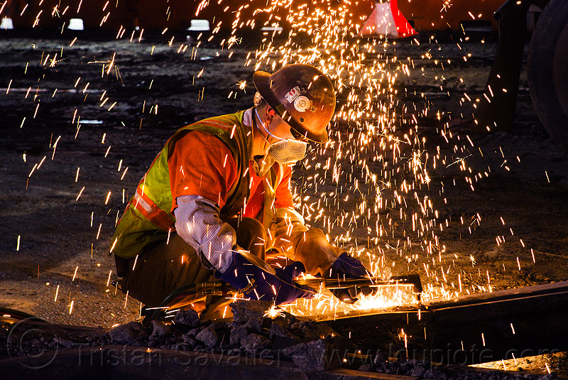 welder using an oxy-acetylene cutting torch, dust mask, high-visibility jacket, high-visibility vest, light rail, man, muni, night, ntk, oxy-acetylene cutting torch, oxy-fuel cutting, railroad construction, railroad tracks, railway tracks, reflective jacket, reflective vest, safety glasses, safety helmet, safety vest, san francisco municipal railway, sparks, track maintenance, track work, welder, worker, working