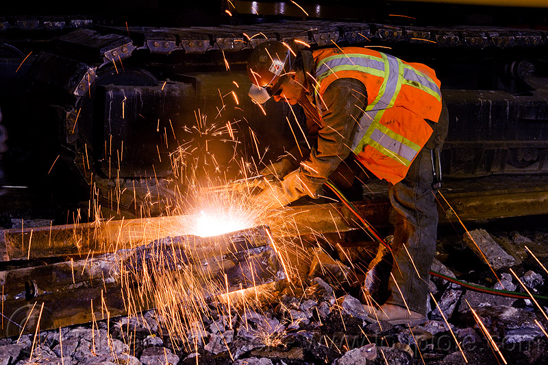 welder using cutting torch to cut a rail, demolition, high-visibility jacket, high-visibility vest, light rail, man, muni, night, ntk, oxy-acetylene cutting torch, oxy-fuel cutting, railroad construction, railroad tracks, railway tracks, reflective jacket, reflective vest, safety helmet, safety vest, san francisco municipal railway, sparks, track maintenance, track work, welder, welding, worker, working