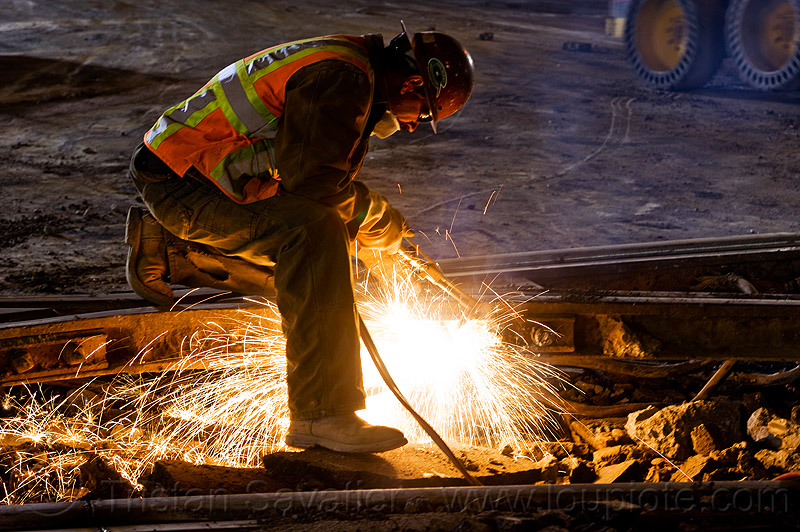 welder using cutting torch to cut a rail, construction, demolition, helmet, high-visibility jacket, high-visibility vest, light rail, man, muni, night, ntk, oxy-acetylene, oxy-acetylene cutting, oxy-acetylene cutting torch, oxy-fuel, oxy-fuel cutting, people, railroad, railroad construction, railroad tracks, rails, railway, railway tracks, reflective, reflective jacket, reflective vest, safety helmet, safety vest, san francisco municipal railway, sparks, track maintenance, track work, welding, worker, working