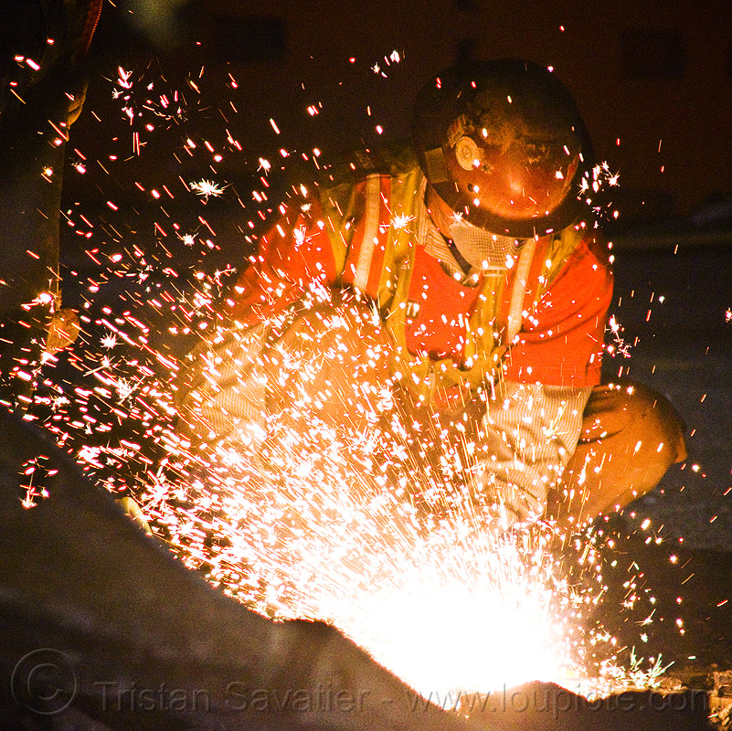 welder using oxy-acetylene cutting torch, construction, helmet, high-visibility jacket, high-visibility vest, light rail, man, muni, night, ntk, oxy-fuel, oxy-fuel cutting, people, railroad, railroad construction, railroad tracks, rails, railway, railway tracks, reflective, reflective jacket, reflective vest, safety glasses, safety helmet, safety vest, san francisco municipal railway, sparks, track maintenance, track work, worker, working