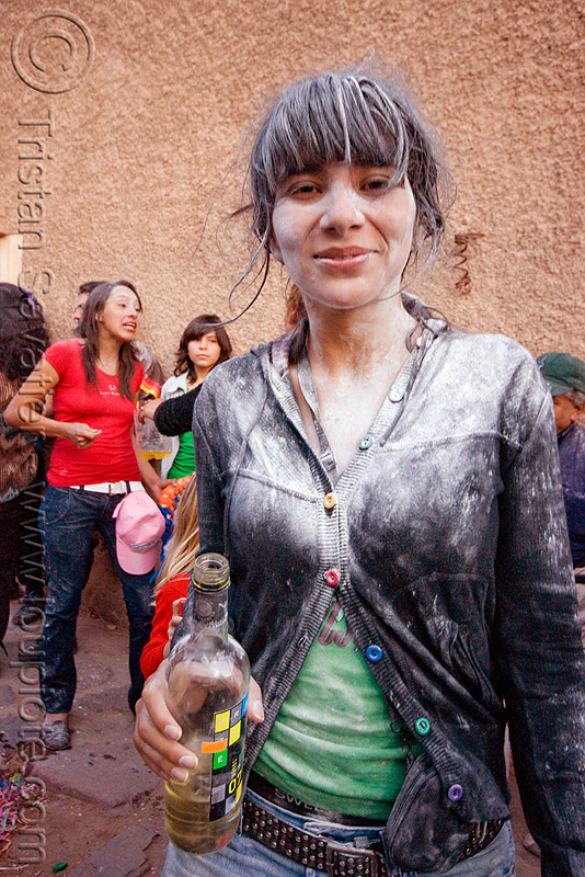white girl with bottle of white wine - carnaval de humahuaca (argentina), andean carnival, argentina, noroeste argentino, quebrada de humahuaca, talk powder, white wine, woman