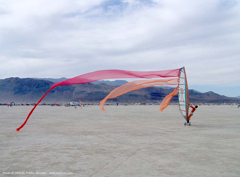 windsurfing on the playa - burning man 2004 - landsailing, burning man, dust storm, landsailing, streamer flags, streamers, street sailing, windsurfing