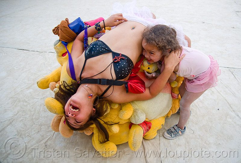 woman and child playing with the pooh-ball - burning man 2009, center camp, kid, people, pooh ball, pooh bear ball, winnie the pooh