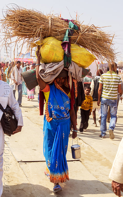 woman carrying bags and hay over head (india), bag, bearer, bundle, carrying on the head, crowd, hay, hindu pilgrimage, hinduism, india, load, luggage, maha kumbh mela, sack, walking