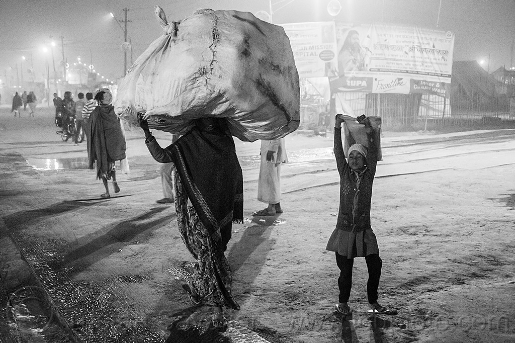 woman carrying huge sack on her head (india), carrying on the head, child, hindu pilgrimage, hinduism, india, kid, large bag, large sack, maha kumbh mela, man, night, pilgrim, porter, walking, woman