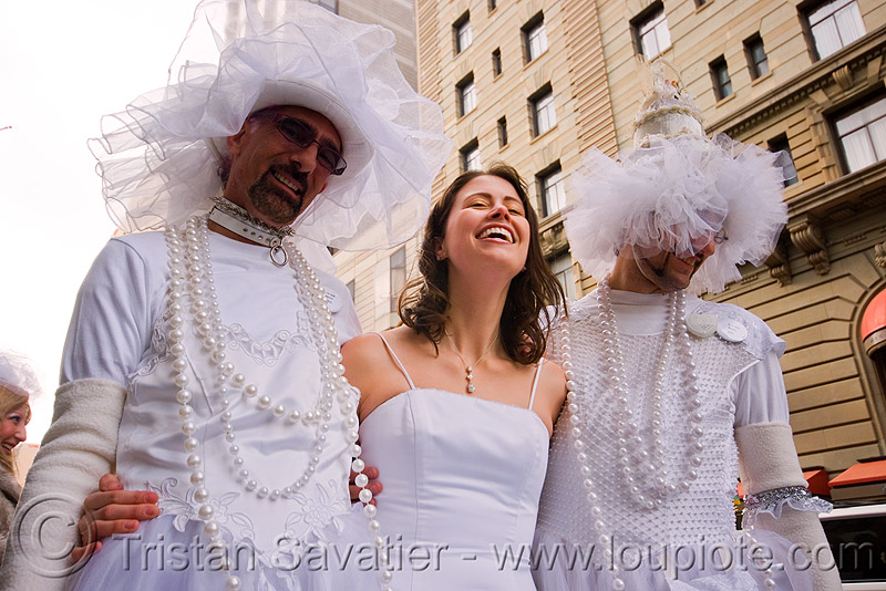 woman laughing between two men dressed as brides - brides of march (san francisco), bride, brides of march, men, necklaces, wedding dress, white, woman