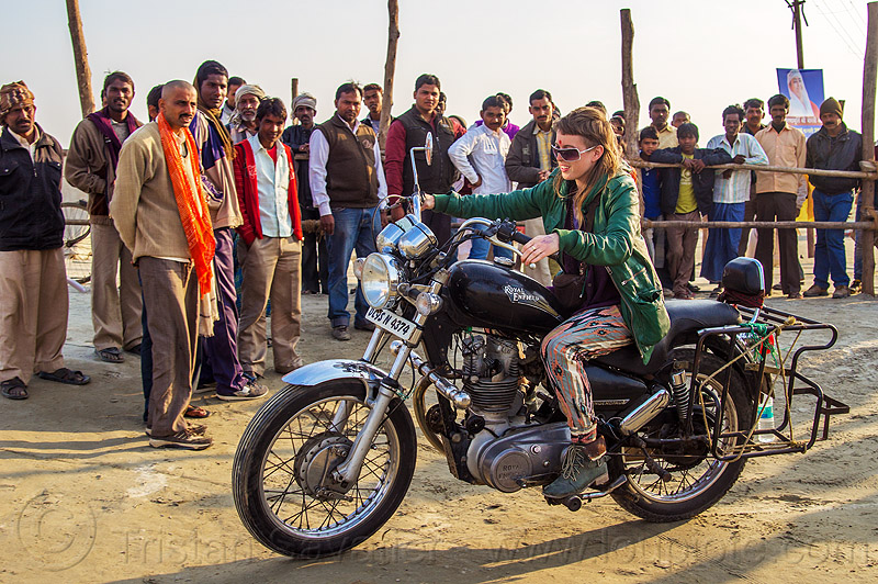 woman riding royal enfield bullet thunderbird motorcycle, 350cc, bun bun, chelsea, crowd, kumbha mela, maha kumbh mela, men, motorbike touring, motorcycle touring, motorcyclist, people, rider, spectators, standing, watching