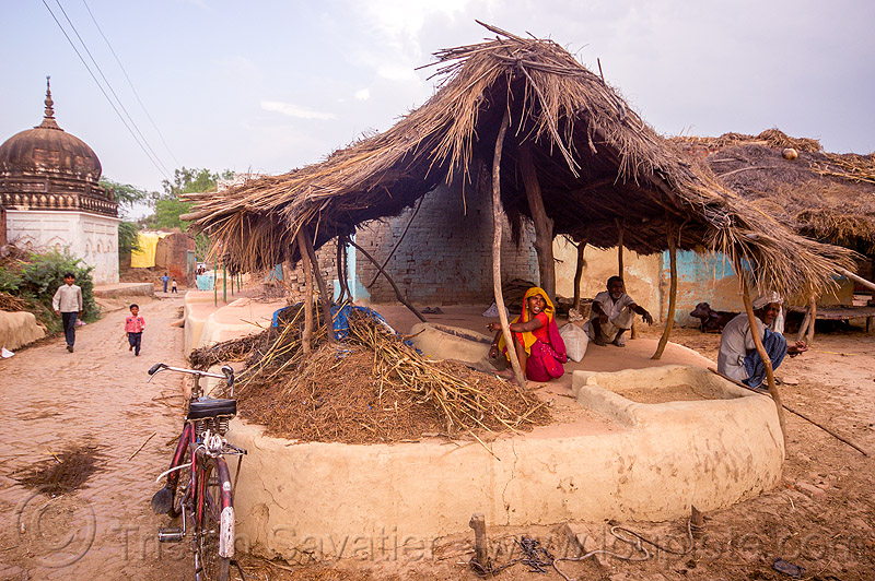 woman sitting in outdoor kitchen in indian village, adobe floor, bicycle, earthen floor, house, khoaja phool, men, monument, people, shrine, street, temple, खोअजा फूल