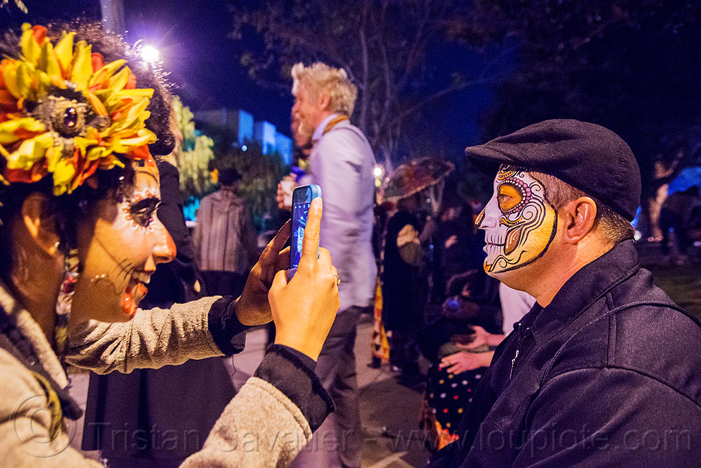 woman taking cellphone photo of man with sugar skull face paint - dia de los muertos, camera, cellphone, day of the dead, dia de los muertos, face painting, facepaint, halloween, hat, man, night, photographer, sahar, sugar skull makeup, taking photo, taking picture, woman