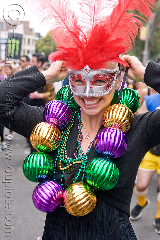 woman with carnival mask and large carnival beads, bay to breakers, costume, feather mask, festival, footrace, mardi gras beads, mardi gras mask, masquerade mask, necklaces, people, red feathers, street party