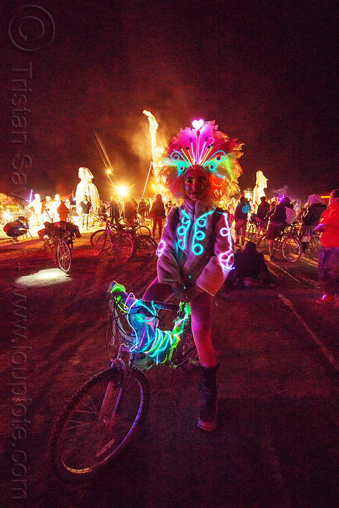woman with glowing EL-wire costume - burning man 2015, bicycle, bike, burning man, costume, crowd, el-wire, feather headdress, feathers, glowing, japanese woman, night