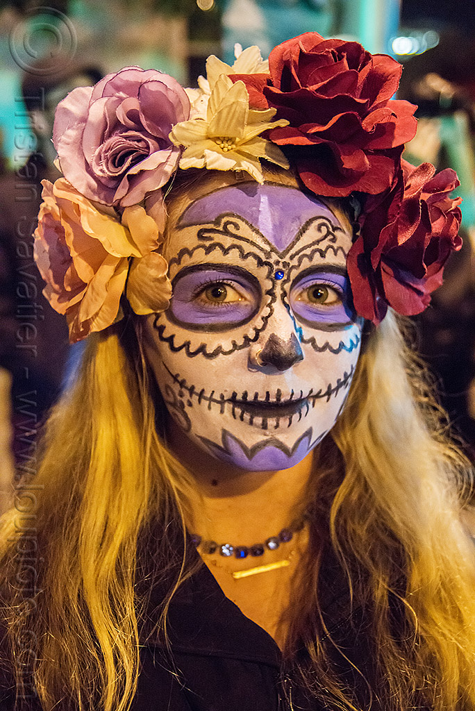 woman with purple and white sugar skull makeup and flower headdress - dia de los muertos, day of the dead, face painting, facepaint, flowers, halloween, neckless, night, people