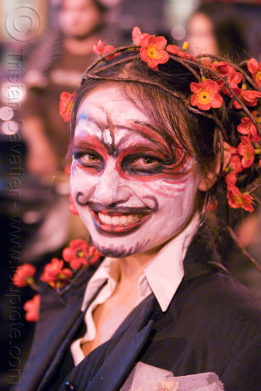woman with red and black face painting - Día de los muertos - halloween (san francisco), day of the dead, dia de los muertos, facepaint, flower headdress, flower headwear, makeup, night, people, red flowers