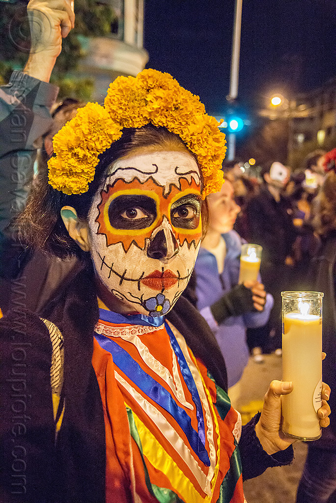 woman with skull makeup - marigold flower headdress - holding glass candle - dia de los muertos, day of the dead, face painting, facepaint, flowers, flowers headdress, halloween, marigold flowers, marigold flowers headdress, night, people, sugar skull makeup