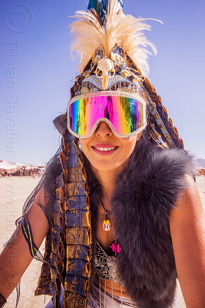 woman with tribal feather headdress and mirror goggles - burning man 2015, bird skull, burning man, costume, fashion, feather headdress, feathers, mirror goggles, rainbow colors, reflection, tribal, woman