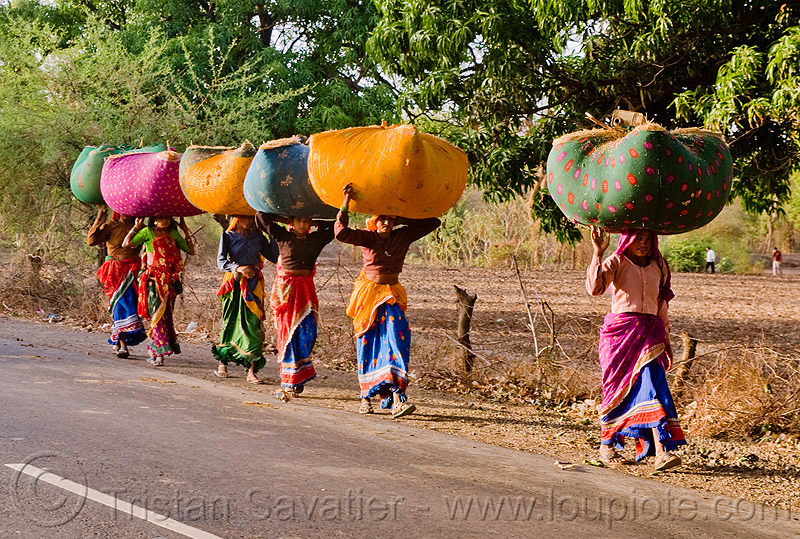 women in sari carrying bags on their head (india), bags, bundles, carrying on the head, colorful, india, road, row, sarees, saris, walking, women