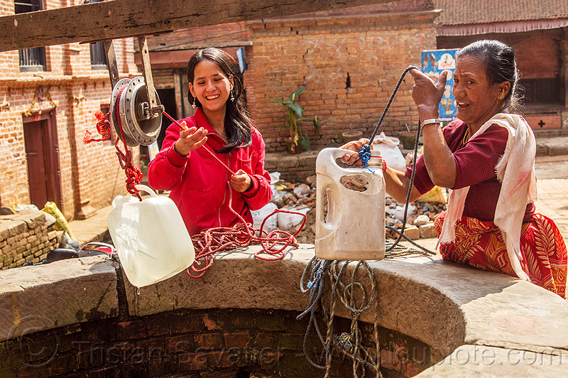 women pulling water jerrycans from water well (nepal), bhaktapur, people, plastic, plastic jerrycans, pulley, ropes
