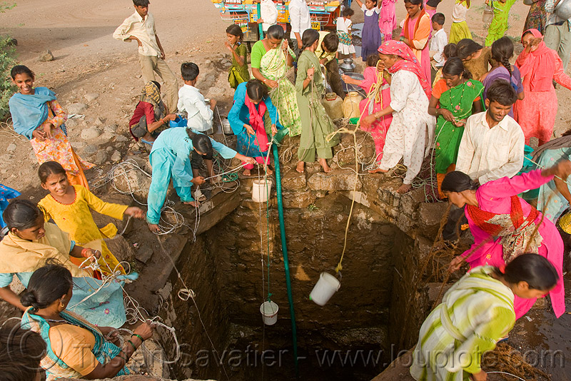 women scooping water with buckets at village water well - ajanta (india), communal water well, crowd, people, ropes, water jars