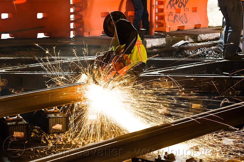 worker cutting track rail with abrasive saw, abrasive saw, cut-off saw, cutting, diamond crossing, high-visibility jacket, high-visibility vest, huskvama, k760, light rail, man, muni, night, ntk, power tool, railroad construction, railroad tracks, railway tracks, reflective jacket, reflective vest, safety helmet, safety vest, san francisco municipal railway, sparks, track maintenance, track work, worker, working