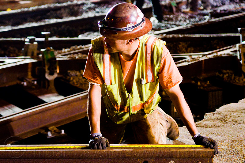 worker measuring rail with tape measure, high-visibility jacket, high-visibility vest, light rail, man, measuring tape, muni, night, ntk, railroad construction, railroad tracks, railway tracks, reflective jacket, reflective vest, safety helmet, safety vest, san francisco municipal railway, tape measure, track maintenance, track work, worker, working