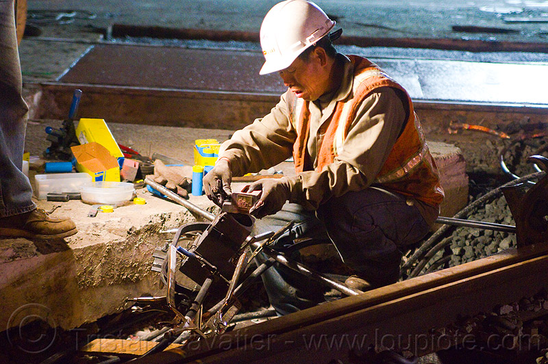 worker prepares a cad-welding crucible, exothermic bonding, exothermic welding, high-visibility jacket, high-visibility vest, light rail, man, muni, night, ntk, people, railroad construction, railroad tracks, rails, railway tracks, reflective jacket, reflective vest, safety helmet, safety vest, san francisco municipal railway, thermite welding, track maintenance, track work, welder, working