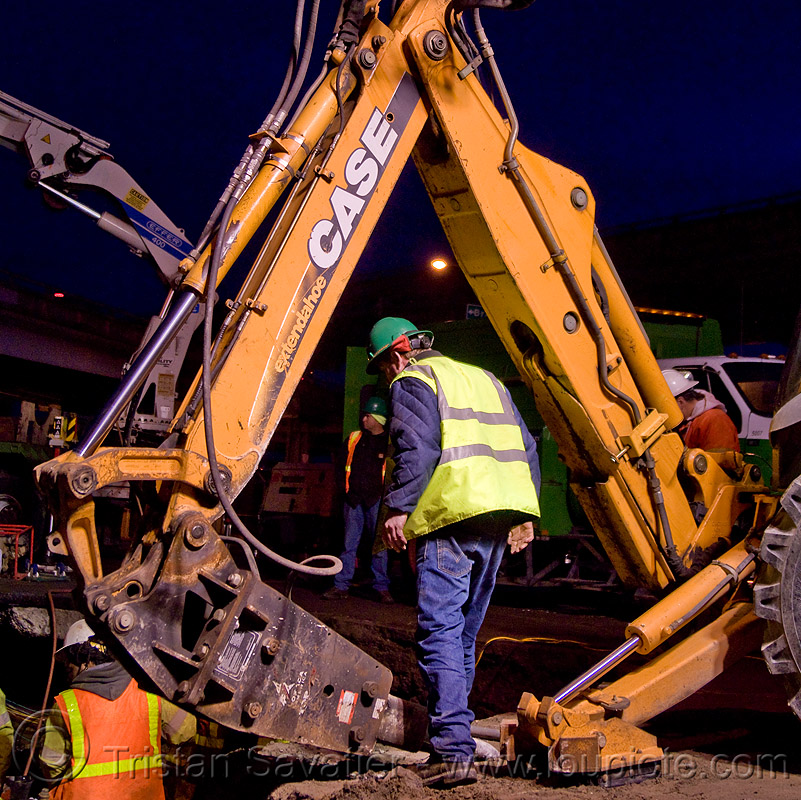 worker under backhoe with hydraulic hammer - utility workers fixing broken water main (san francisco), attachment, case, construction, construction workers, contractor, extendahoe, heavy equipment, hetch hetchy water system, high-visibility vest, hydraulic attachment, infrastructure, machinery, night, people, reflective vest, repairing, safety helmet, safety vest, sfpuc, sink hole, utility crew, water department, water pipe, working