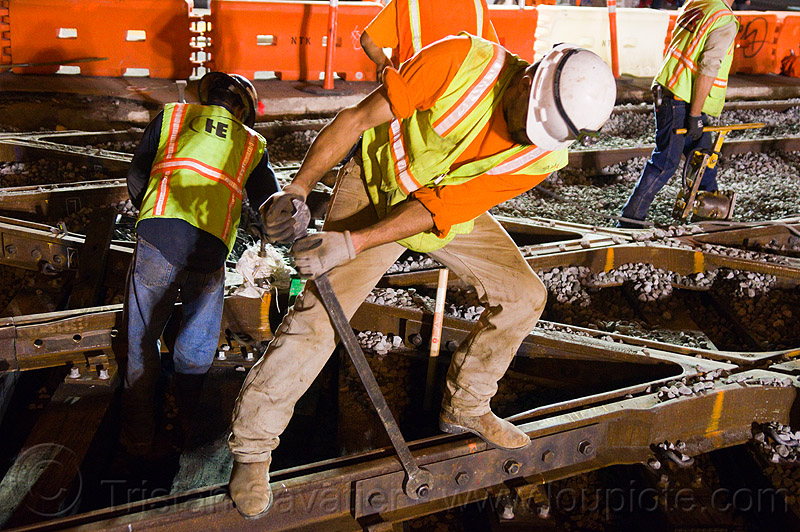 worker unscrewing rail fish plate -  - muni railway construction site (san francisco), bolting, bolts, diamond crossing, fish plate, high-visibility jacket, high-visibility vest, light rail, man, muni, ntk, railroad construction, railroad tracks, railway tracks, reflective jacket, reflective vest, safety helmet, safety vest, san francisco municipal railway, screwing, screws, track maintenance, track work, worker, working, wrench