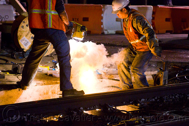 workers ignite cad-weld powder in a crucible, cad-welding, exothermic bonding, exothermic welding, high-visibility jacket, high-visibility vest, light rail, men, muni, night, ntk, railroad construction, railroad tracks, rails, railway tracks, reflective jacket, reflective vest, safety helmet, safety vest, san francisco municipal railway, thermite welding, track maintenance, track work, welder, workers, working