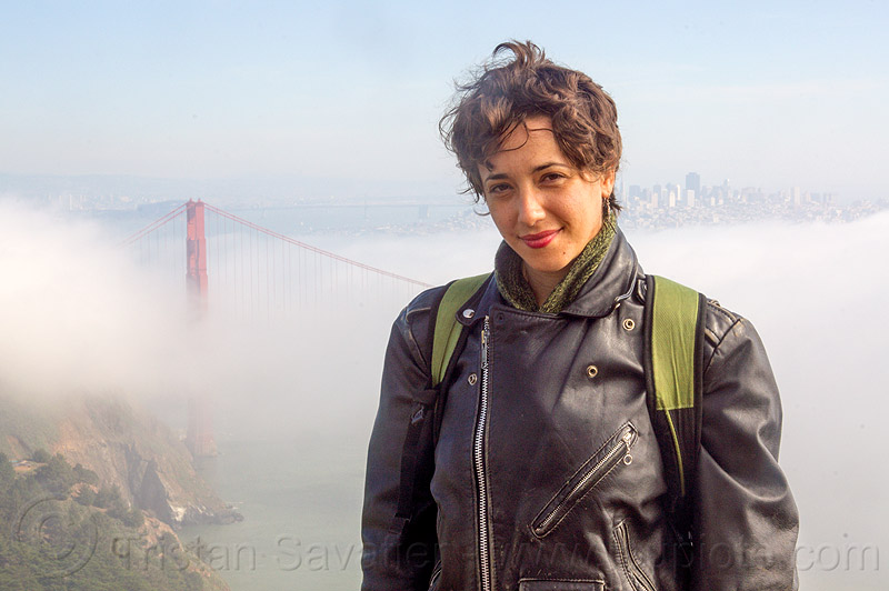 yassmine wearing a leather motorcycle jacket (san francisco), fog, golden gate bridge, leather jacket, motorcycle jacket, standing, suspension bridge, woman, yassmine