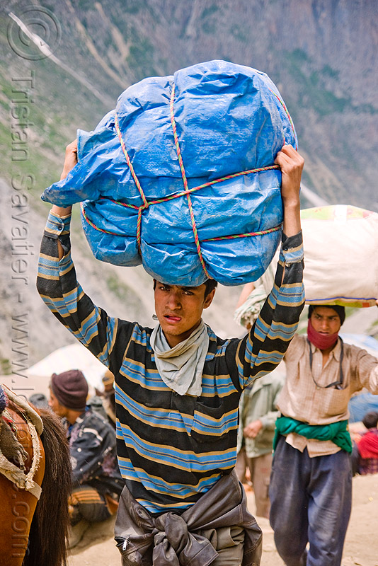 young porter carrying heavy load on his head - amarnath yatra (pilgrimage) - kashmir, amarnath yatra, bag, bearer, blue, carrying on the head, kashmir, men, mountain trail, mountains, pilgrim, pilgrimage, porter, ropes, tarp, trekking, wallah, yatris, अमरनाथ गुफा