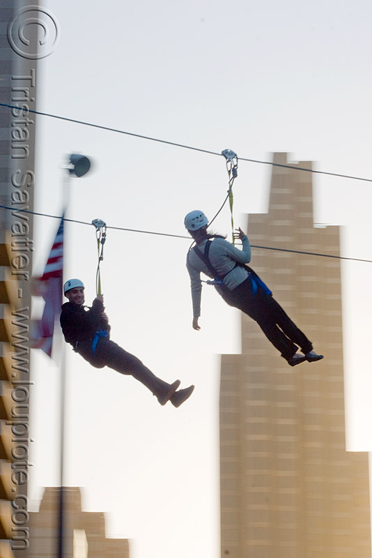 zip-line over san francisco, adventure, american flag, buildings, cable line, cables, climbing helmet, embarcadero, extreme sport, flag pole, gear, hanging, harness, high-rise, justin herman plaza, mountaineering, moving fast, speed, steel cable, tower, trolley, two, tyrolienne, urban, us flag, zip line, zip wire, ziptrek