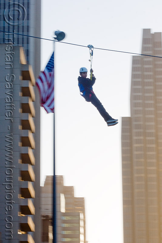 zip-line over san francisco, adventure, american flag, blue sky, buildings, cable line, cables, climbing helmet, embarcadero, flag pole, hanging, high-rise, mountaineering, moving fast, speed, steel cable, tower, trolley, tyrolienne, urban, us flag, zip line, zip wire