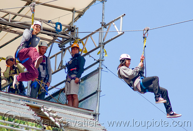 zoey riding the zip-line over san francisco, adventure, blue sky, cable line, cables, climbing helmet, embarcadero, hanging, jump, mountaineering, moving fast, speed, start, steel cable, tower, trolley, tyrolienne, urban, woman, zip line, zip wire