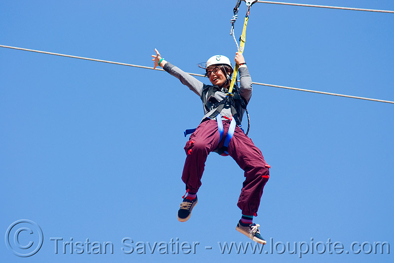 zoey riding the zip-line over san francisco, adventure, blue sky, cable line, cables, climbing helmet, embarcadero, hanging, mountaineering, moving fast, speed, steel cable, trolley, tyrolienne, urban, woman, zip line, zip wire