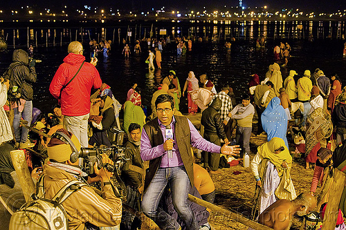 ABP news live TV reporter covers the holy bath at kumbh mela 2013 (india), abp news, broadcasting, camera, cameraman, crowd, fence, ganga, ganges river, hindu pilgrimage, hinduism, holy bath, holy dip, india, journalist, line broadcast, maha kumbh mela, men, mic, microphone, nadi bath, night, paush purnima, pilgrims, reporter, ritual bath, river bank, river bathing, street lights, triveni sangam, tv news, women