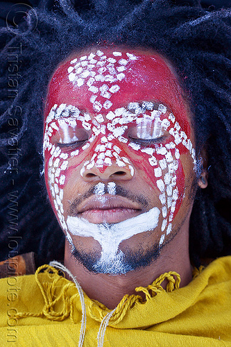 african face paint, african american man, african face paint, black man, dreadlocks, eyes closed, eyes shut, face painting, facepaint, indigenous culture, jason, lying down, makeup, red, tribal face paint, white dots, yellow tunic