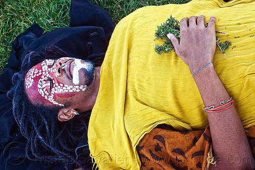 african shaman with tribal face paint, african american man, african face paint, black man, bracelet, dreadlocks, earring, eyes closed, eyes shut, face painting, facepaint, herbs, jason, lawn, lying down, makeup, red, redhead, tribal face paint, white, yellow tunic