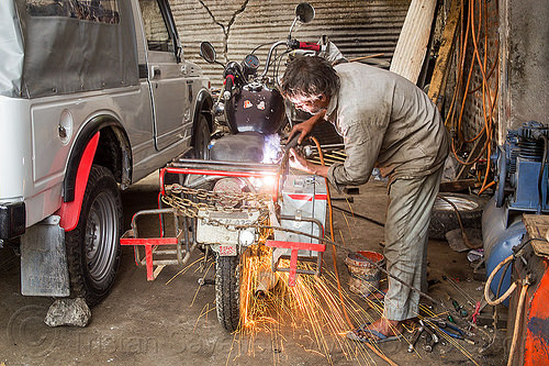 arc welding repair on motorbike (india), 350cc, arc welding, fixing, man, mechanic, motorcycle, repairing, royal enfield bullet, shock absorber, sikkim, sparks, thunderbird, welder, worker, working