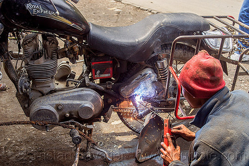 arc welding repair on motorbike rack - royal enfield bullet (india), 350cc, arc welding, fixing, luggage rack, man, mechanic, motorcycle, repairing, royal enfield bullet, sikkim, sparks, thunderbird, welder, worker, working