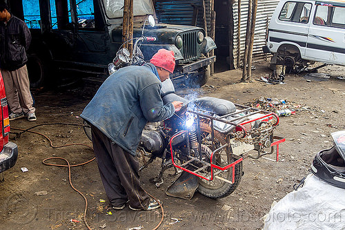 arc welding repair on motorbike rack - royal enfield bullet (india), 350cc, arc welding, fixing, luggage rack, man, mechanic, motorbike, motorcycle, repairing, royal enfield bullet, sikkim, thunderbird, welder, worker, working