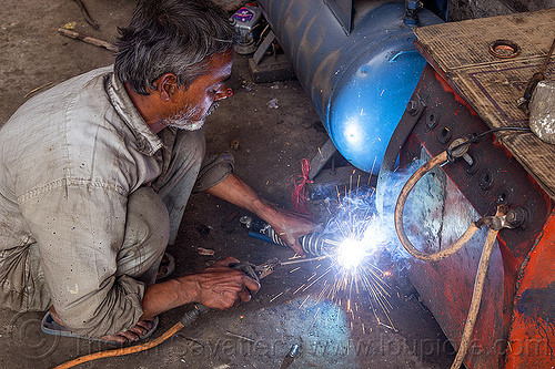 arc welding repair on motorbike shock (india), 350cc, bullet, fixing, man, mechanic, motorcycle, people, repairing, royal enfield, royal enfield bullet, shock absorber, sikkim, sparks, thunderbird, welder, worker, working