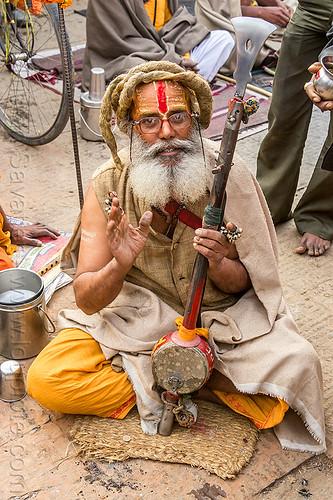 baba (hindu devotee) with musical instrument (nepal), baba, cross-legged, dreads, festival, hindu, hinduism, kathmandu, maha shivaratri, man, pashupati, pashupatinath, sadhu, sitting, tilak, tilaka, white beard