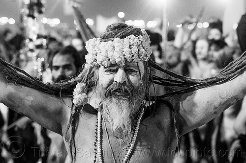 baba (hindu holy man) with marigold flower crown and long dreadlocks - kumbh mela festival (india), crowd, dawn, flower necklaces, hindu, hinduism, kumbha mela, maha kumbh mela, marigold flowers, men, naga babas, naga sadhus, naked, night, orange flowers, procession, sadhu, triveni sangam, vasant panchami snan, walking