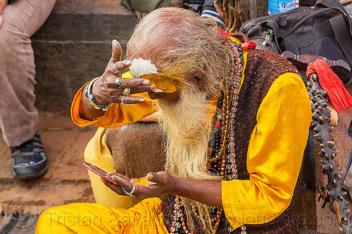 baba making tilaka mark on forehead (nepal), baba, beads, beard, bhagwa, bracelets, festival, finger rings, hindu, hinduism, kathmandu, maha shivaratri, man, necklaces, pashupati, pashupatinath, sadhu, saffron color, talak, tilak, tilaka
